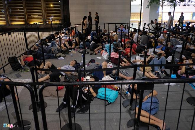 Người Việt Nam vạ vật xếp hàng trong mưa trước cửa Apple Store ở Singapore chờ mua iPhone XS