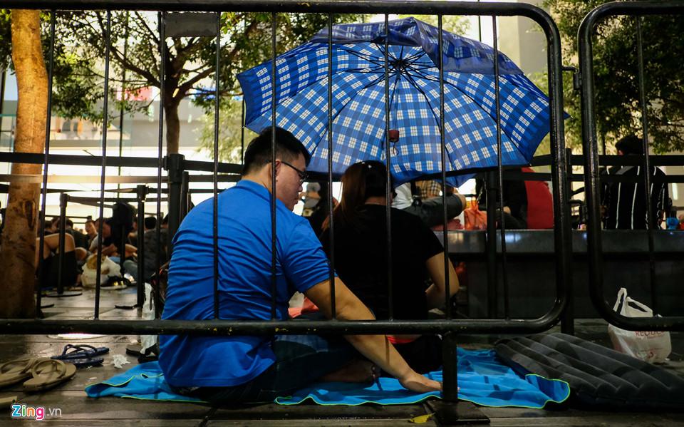 Nhiều người Việt qua đêm ngoài mưa chờ mua iPhone XS. Sau một ngày dầm mưa dãi nắng, hàng trăm người chờ mua iPhone XS đã thấm mệt. Họ tìm bất cứ chỗ trống nào để có thể ngả lưng.