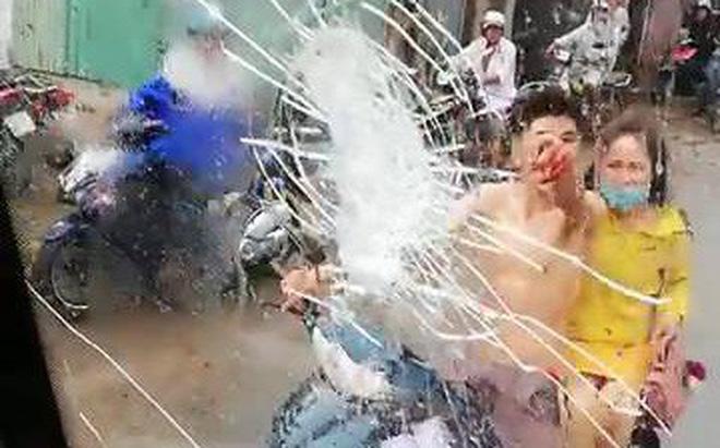 Bị ô tô chạy qua chẳng may tạt nước vào người, nam thanh niên chở bạn gái đuổi theo, cầm gạch ném vỡ kính xe