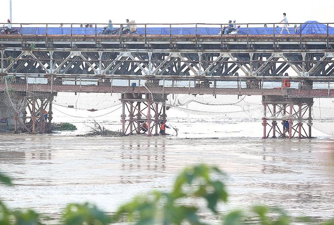 Tại đoạn cầu Long Biên đang thi công bảo dưỡng, nhóm thợ sửa chữa cầu phải tập trung dọn rác kẹt dưới chân cầu.