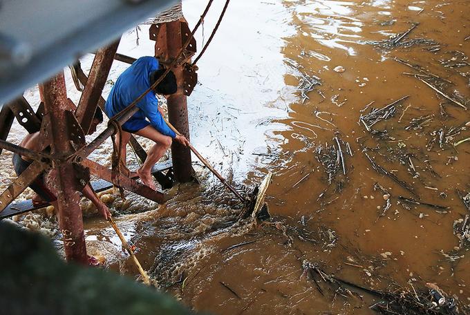 Trụ cầu tạm bằng kim loại, được dựng lên để bảo dưỡng cầu Long Biên. Nếu đẩy rác trôi nổi kẹt vào các trụ này thì nguy cơ rác đọng có khiến nước cuốn cả chân cầu đi gây nguy hiểm cho cầu.