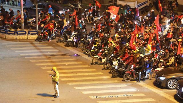 """Mặc dù """"đi bão"""" ăn mừng chiến thắng của thầy trò HLV Park Hang Seo nhưng người hâm mộ vẫn không quên dừng đèn đỏ, tuân thủ luật giao thông. (Nguồn: Cafebiz.vn)"""