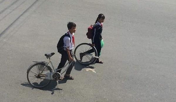 Hài hước hình ảnh học sinh dắt xe đạp đi ngoài trời nắng: Đứa cầm bánh trước, đứa dắt thân sau