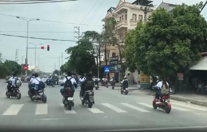 Ngán ngẩm hàng chục học sinh đi xe đạp điện ngang nhiên cùng nhau vượt đèn đỏ