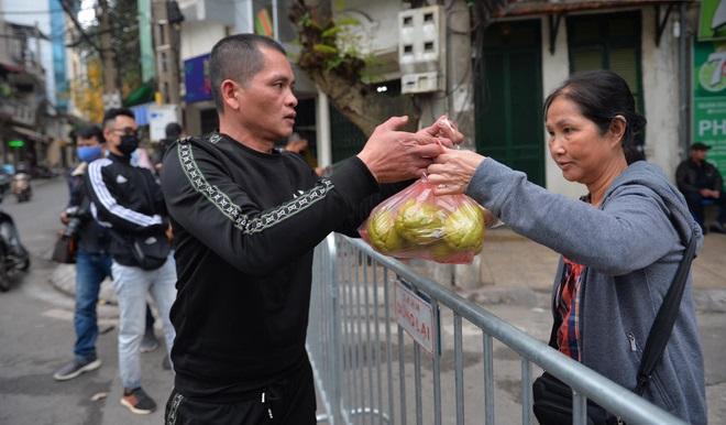 Ngày đầu cách ly Covid-19 tại khu phố Trúc Bạch, các hộ nhận đồ tiếp tế qua hàng rào chắn
