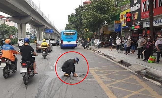 Người đàn ông đi xe máy làm rớt dầu nhớt ra đường, liền xuống xe lau sạch hết rồi mới đi tiếp