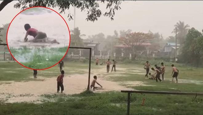 Mưa lớn biến sân bóng thành sông, lũ trẻ vẫn say sưa chơi bóng và tranh thủ tắm mưa khiến bao người thèm thuồng